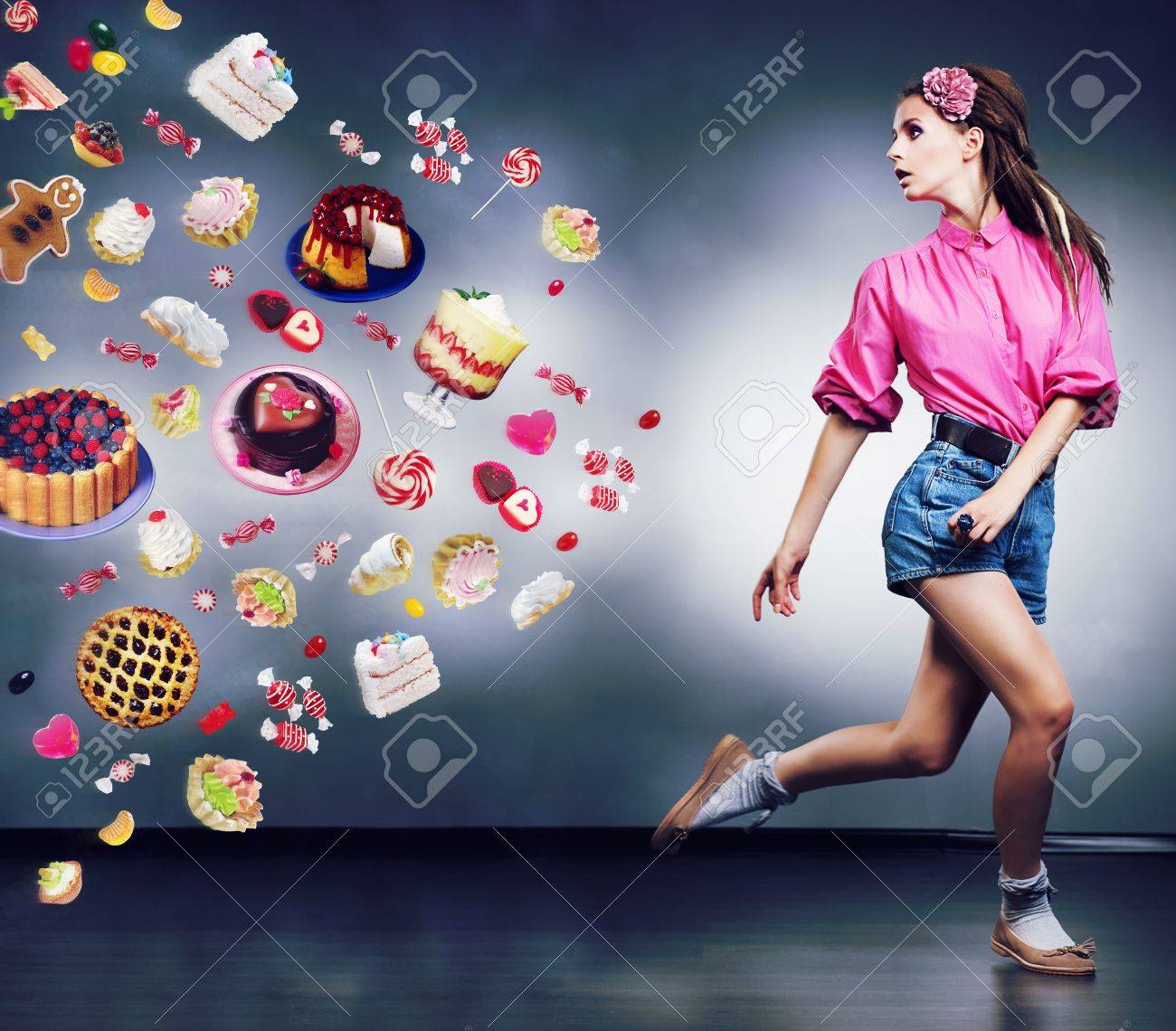 Escape. Resolute running woman refuses to eating tasty cakes and chocolate. Diet concept Stock Photo - 16319011