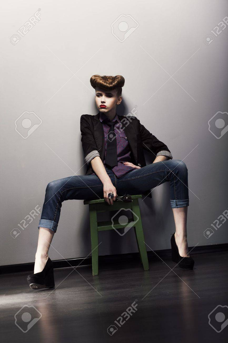 Pin up retro woman sitting in jeans and stylish jacket. Bright hairstyle Stock Photo - 16319007