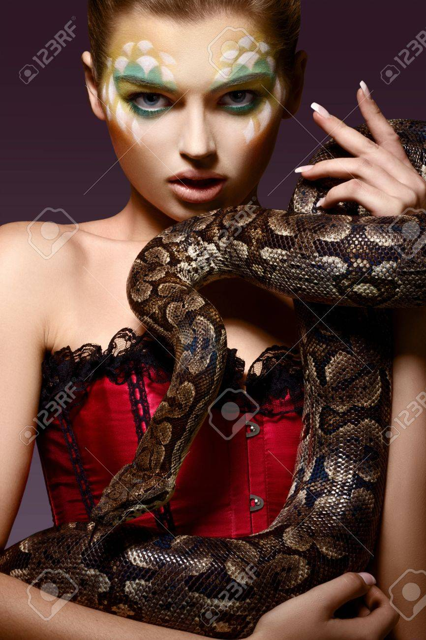 Serpent. Fantasy. Fancy Woman holding Tamed Snake in Hands Stock Photo - 17602578
