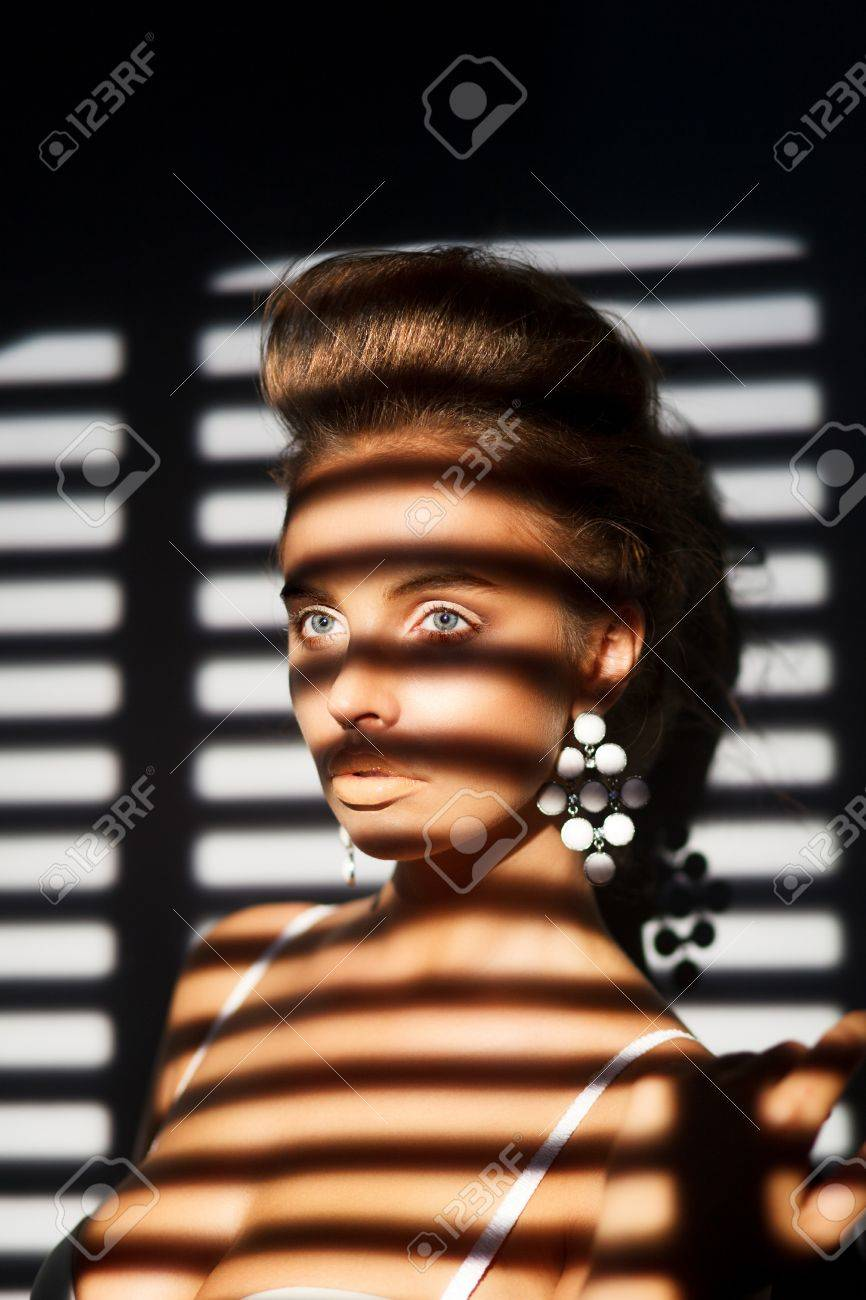 Charisma. Charming Woman's Face in Shadow of Roller Blind Stock Photo - 17934703