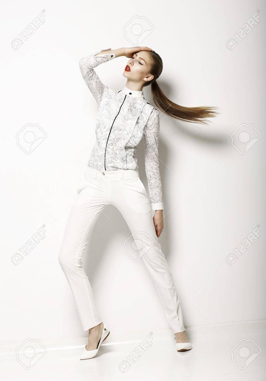 5149fb200 Ropa de diseño contemporáneo. Mujer de moda del en blusa blanca y  pantalones. Moda