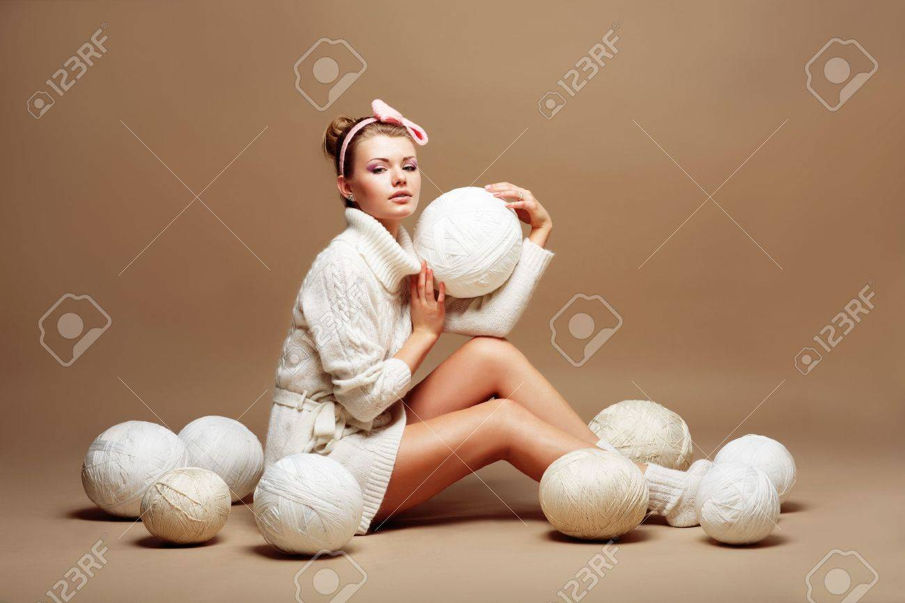 Knitting. Sewing. Woman in White Knitted Clothing with Bulk of Fluffy Clews of Yarn Stock Photo - 19386426