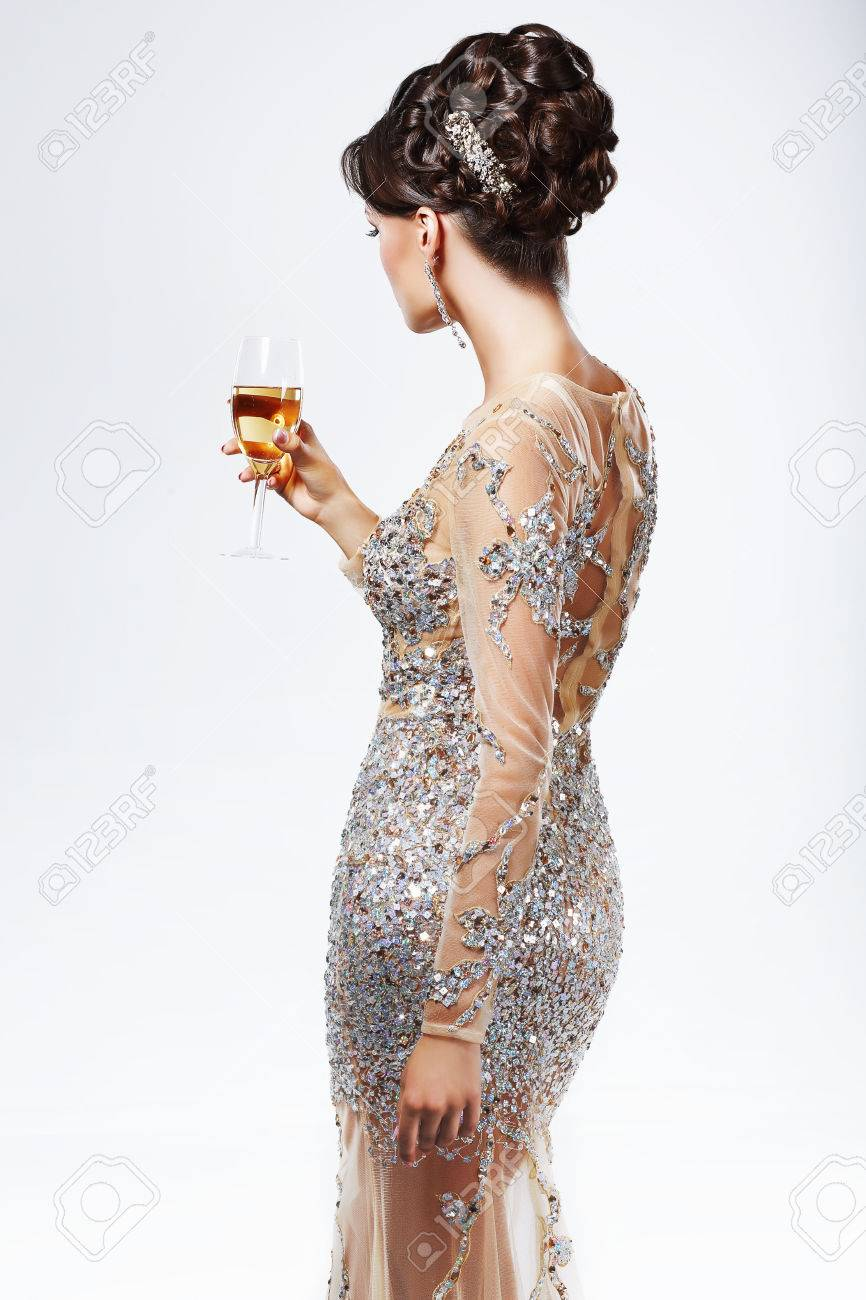 elegante frau in silber-golden kleid hält weinglas champagner. luxus