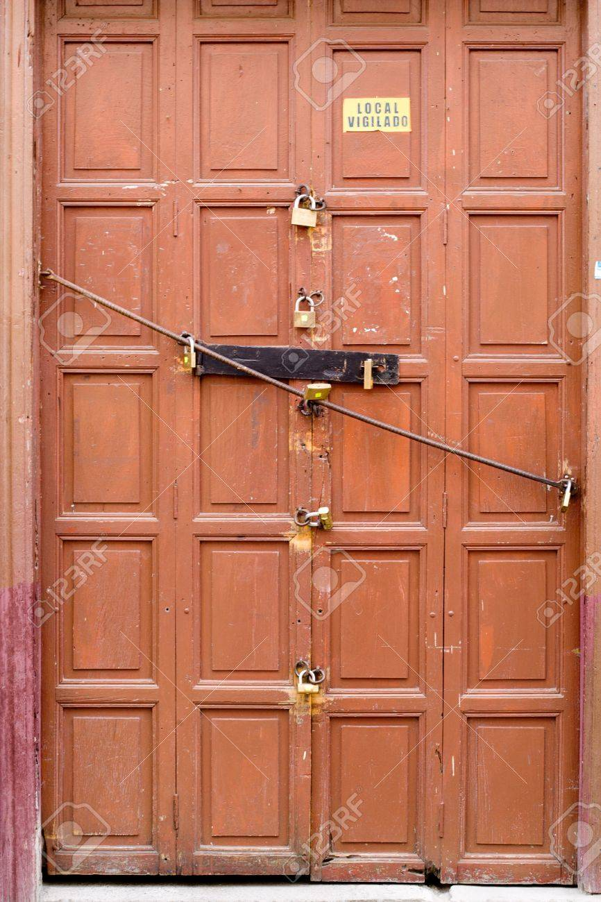 8 locks on an old brwon door, Loja Ecuador   editorial  Stock Photo - 16895917