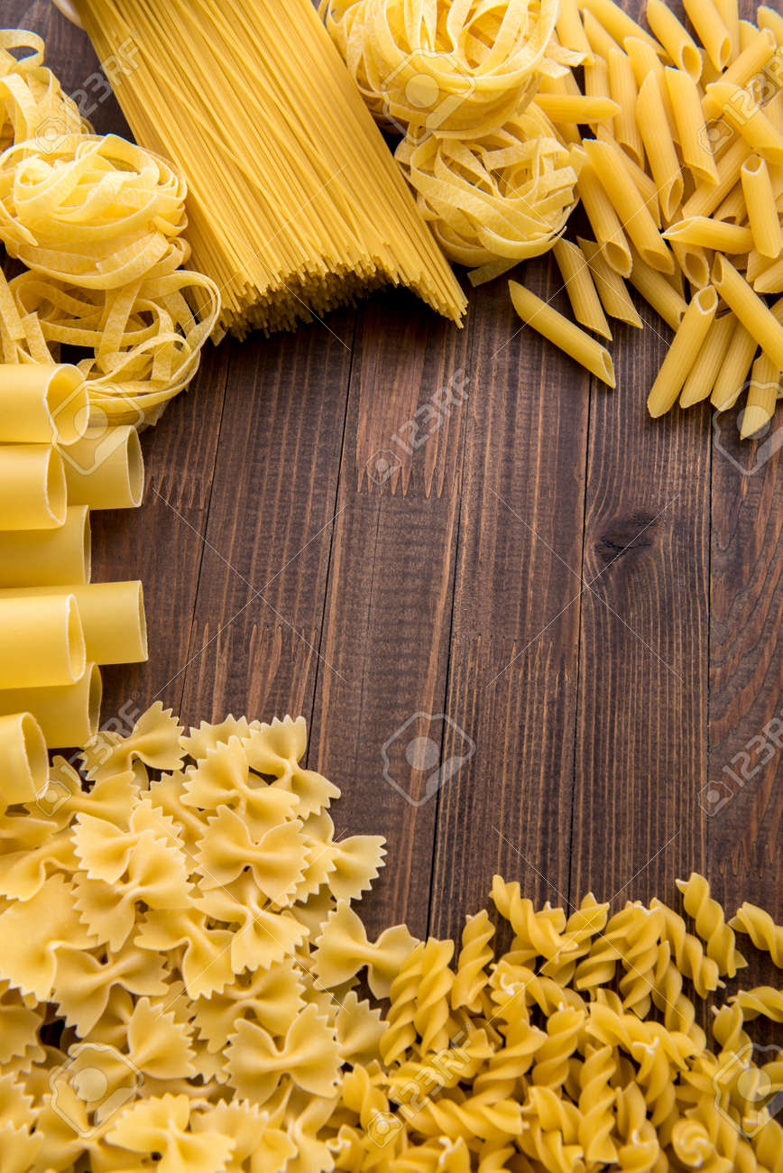 Different kinds of pasta on a wooden background. Farfalle, fettuccine, noodles. - 167806651