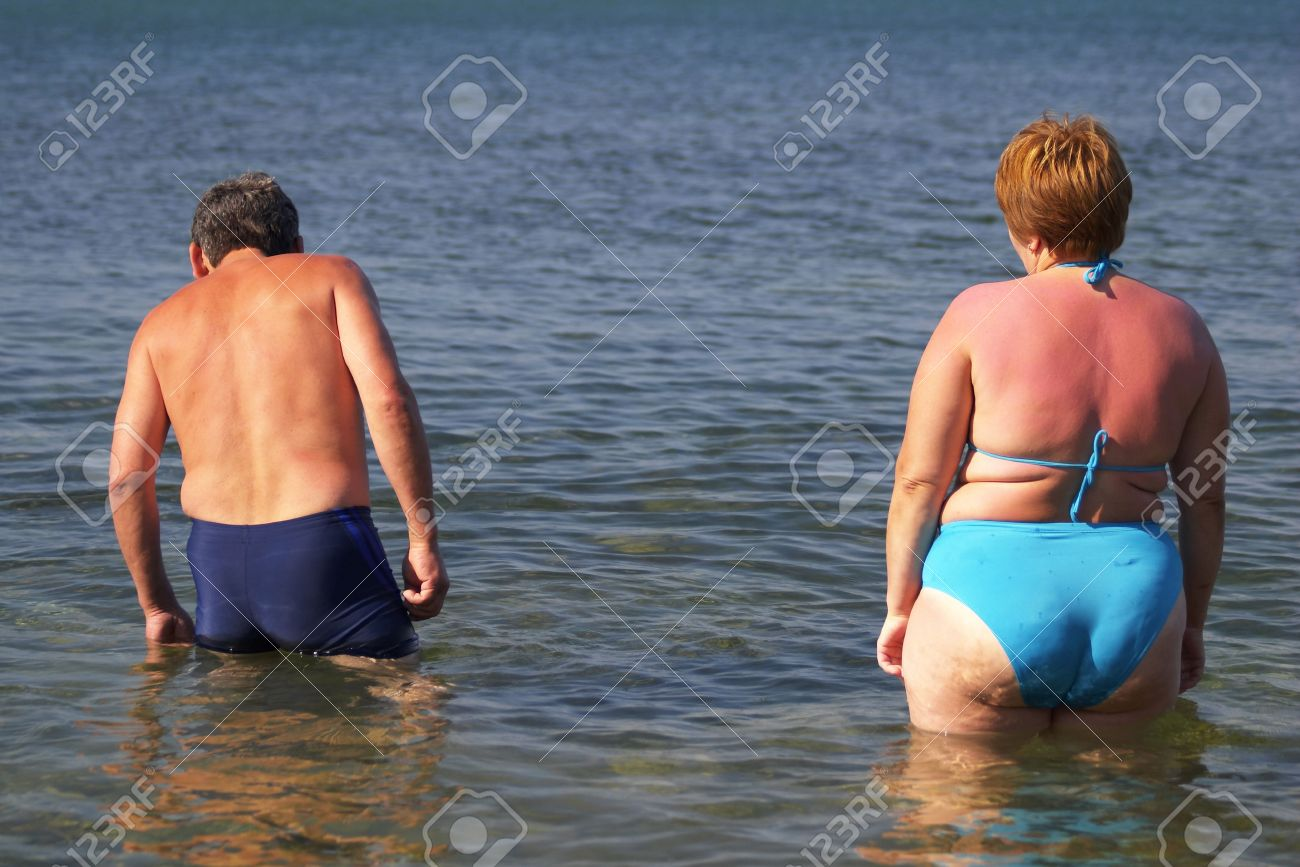 rear view of a man and woman standing in the sea stock photo