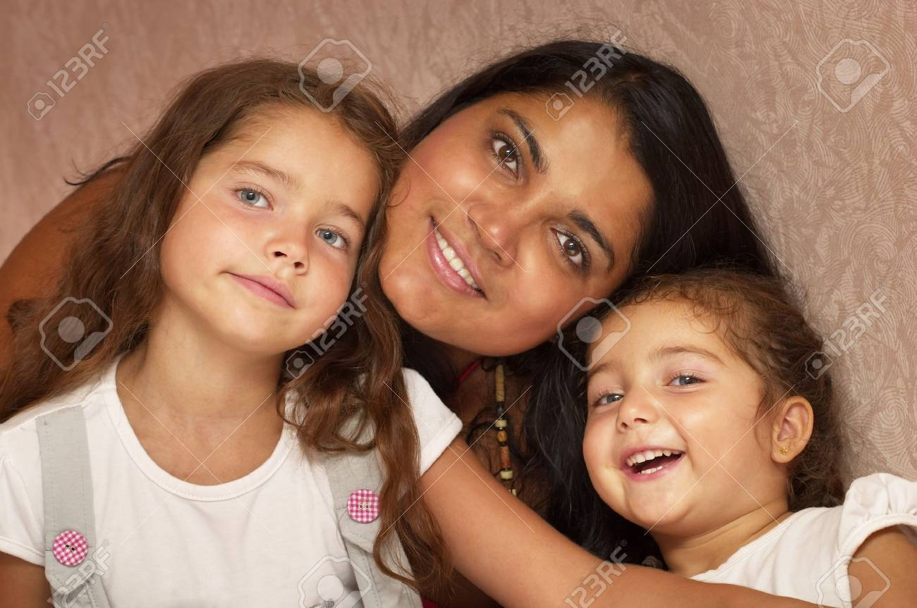 Young mother and two little sisters over defocused wallpaper background Stock Photo - 7533072