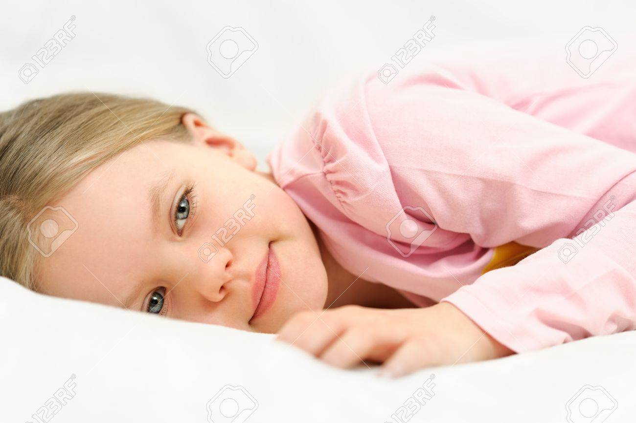 Young little girl is laying on bed with peaceful face expression Stock Photo - 18267758
