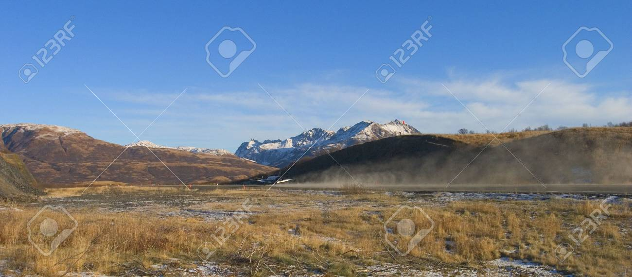 plane taking off on a dirt runway with snow Stock Photo - 2949249
