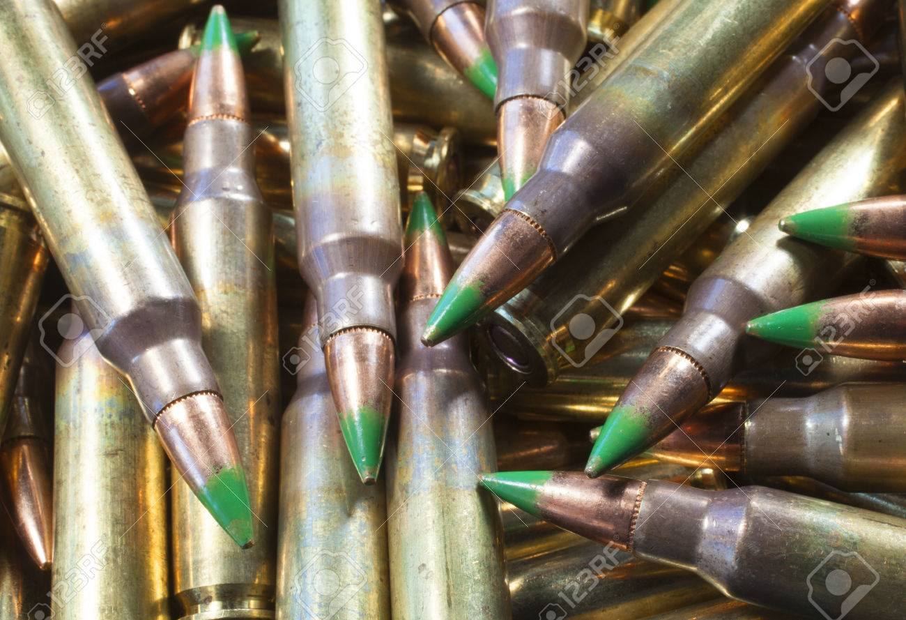 ammunition with bullets with a green tip in a big pile stock photo