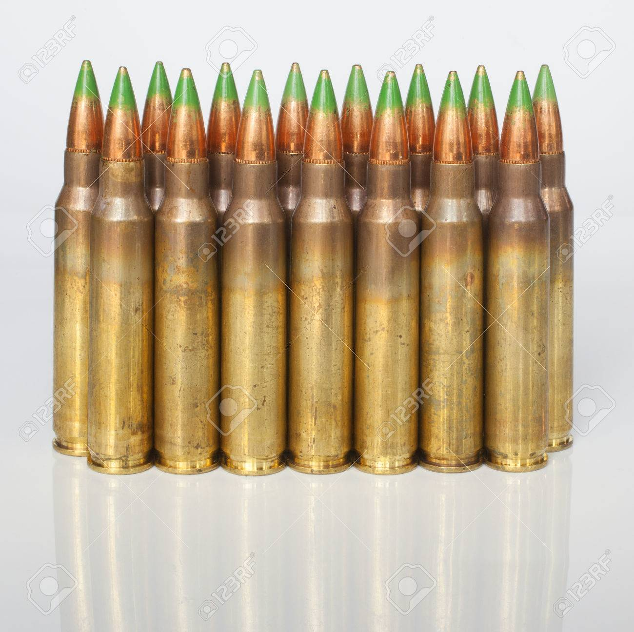 cartridges loaded with bullets that have a green tip on a white