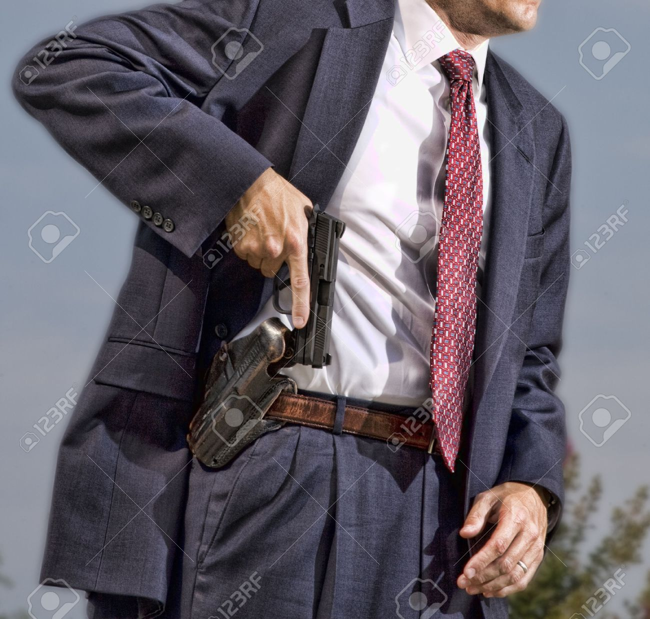 Person with a concealed carry permit starting to draw his handgun - 63414067