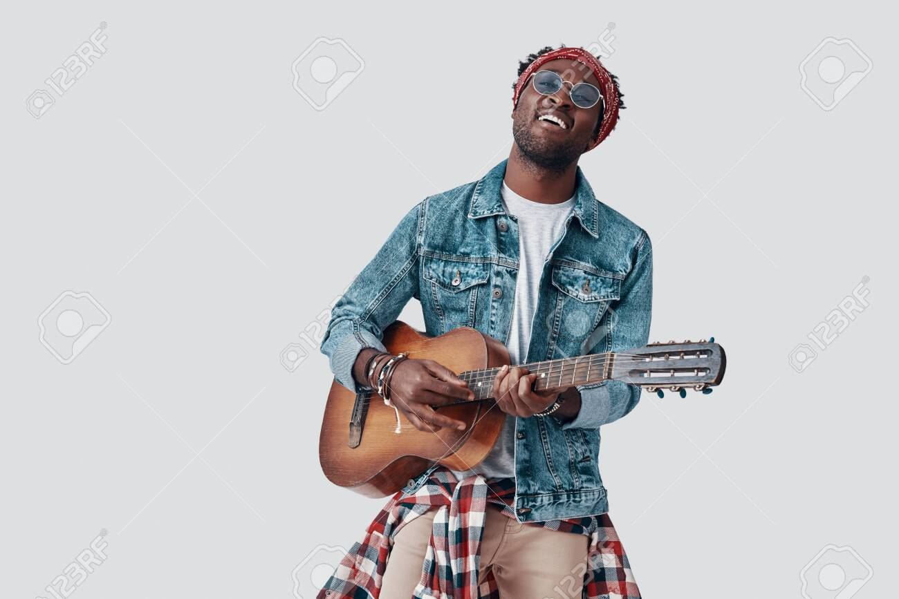 Handsome young African man playing guitar and smiling while standing against grey background - 135471600