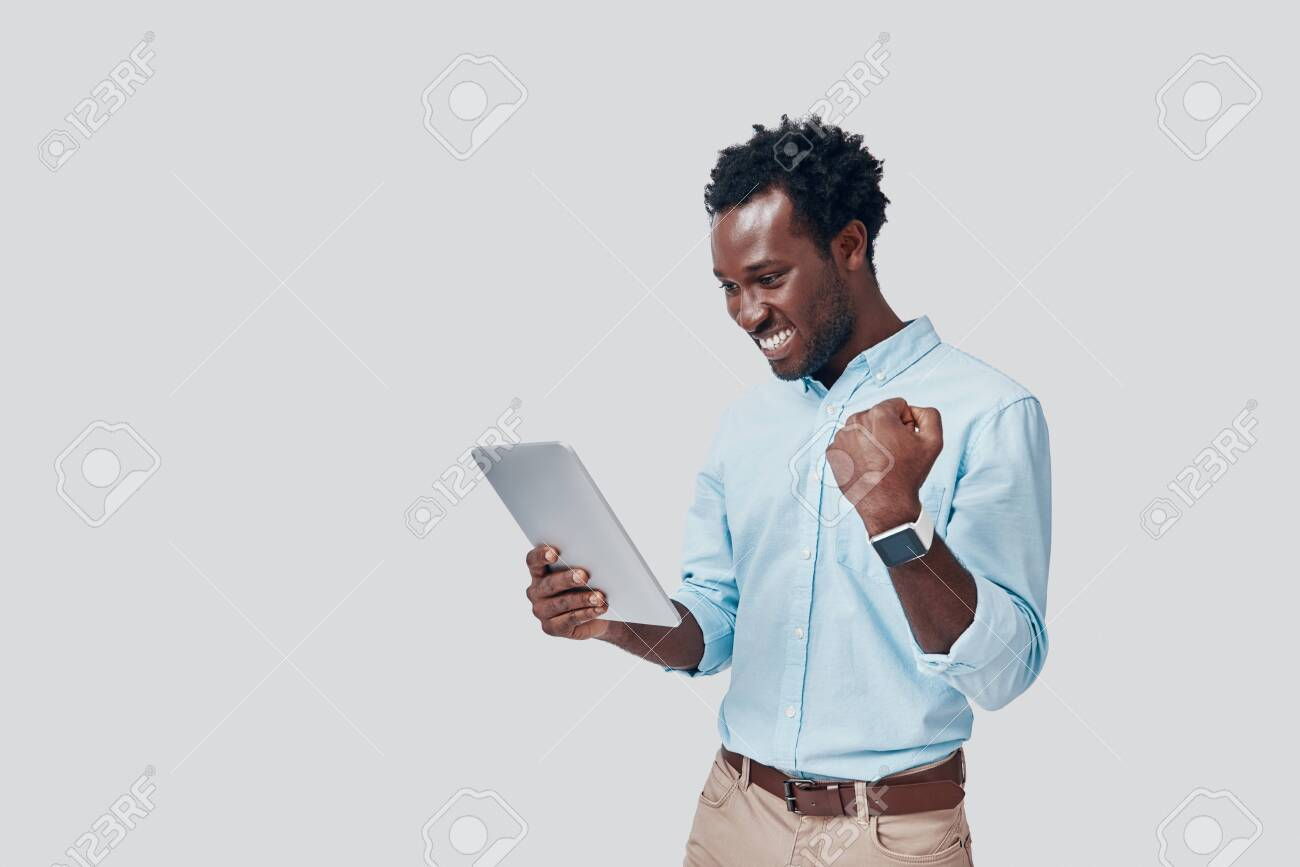 Handsome young African man using digital tablet and cheering while standing against grey background - 135471603