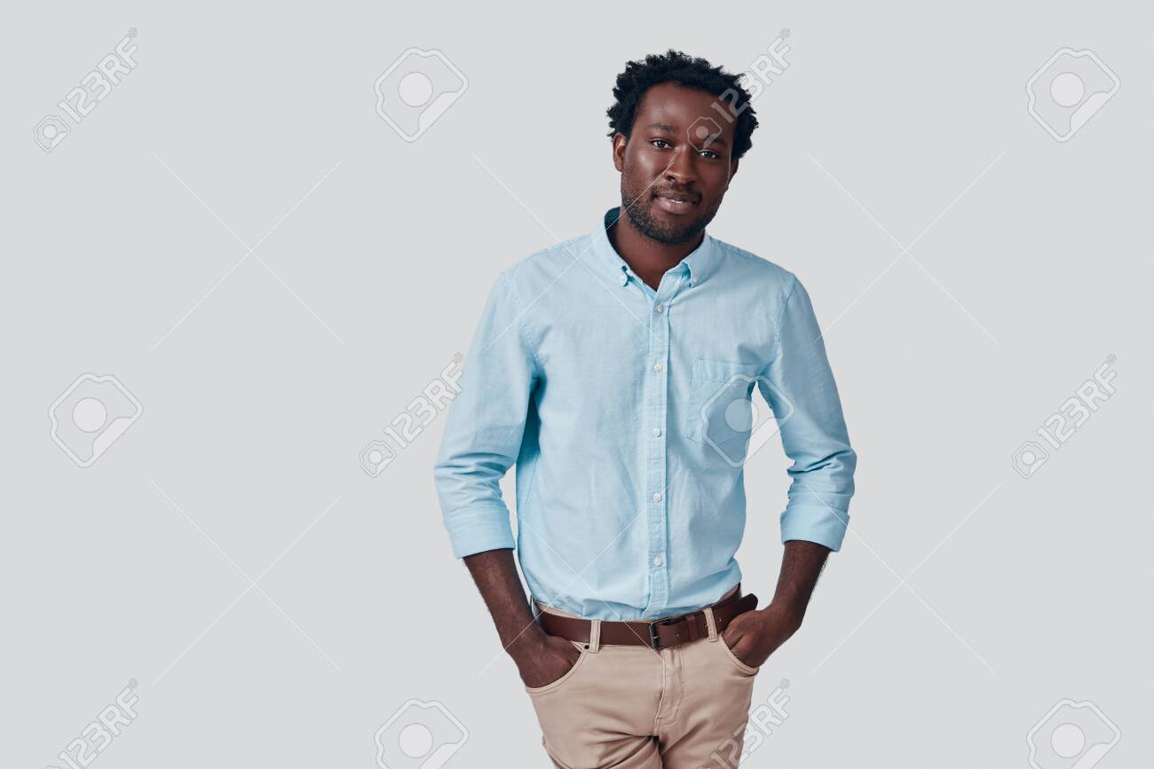 Handsome young African man looking at camera and smiling while standing against grey background - 135471605