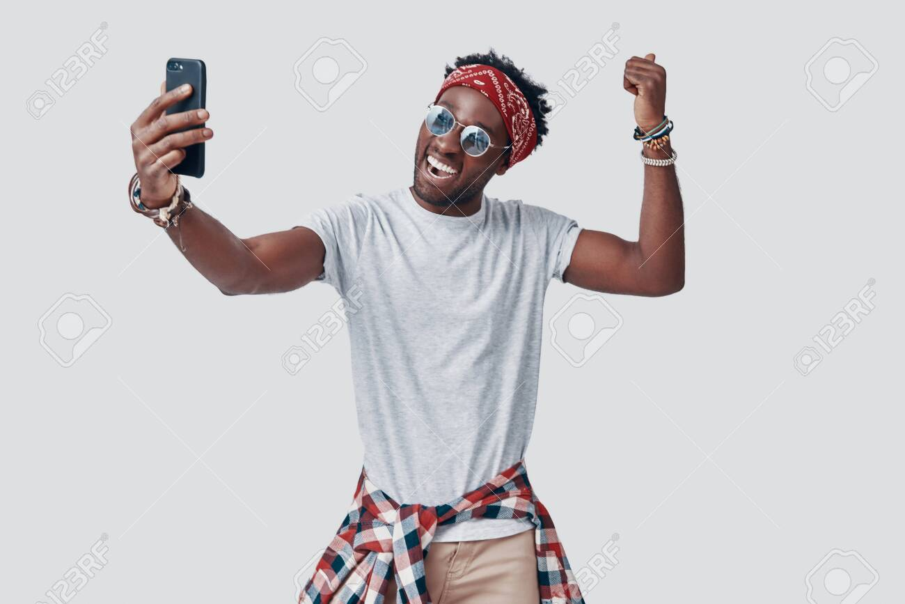 Handsome young African man taking selfie and smiling while standing against grey background - 135471608