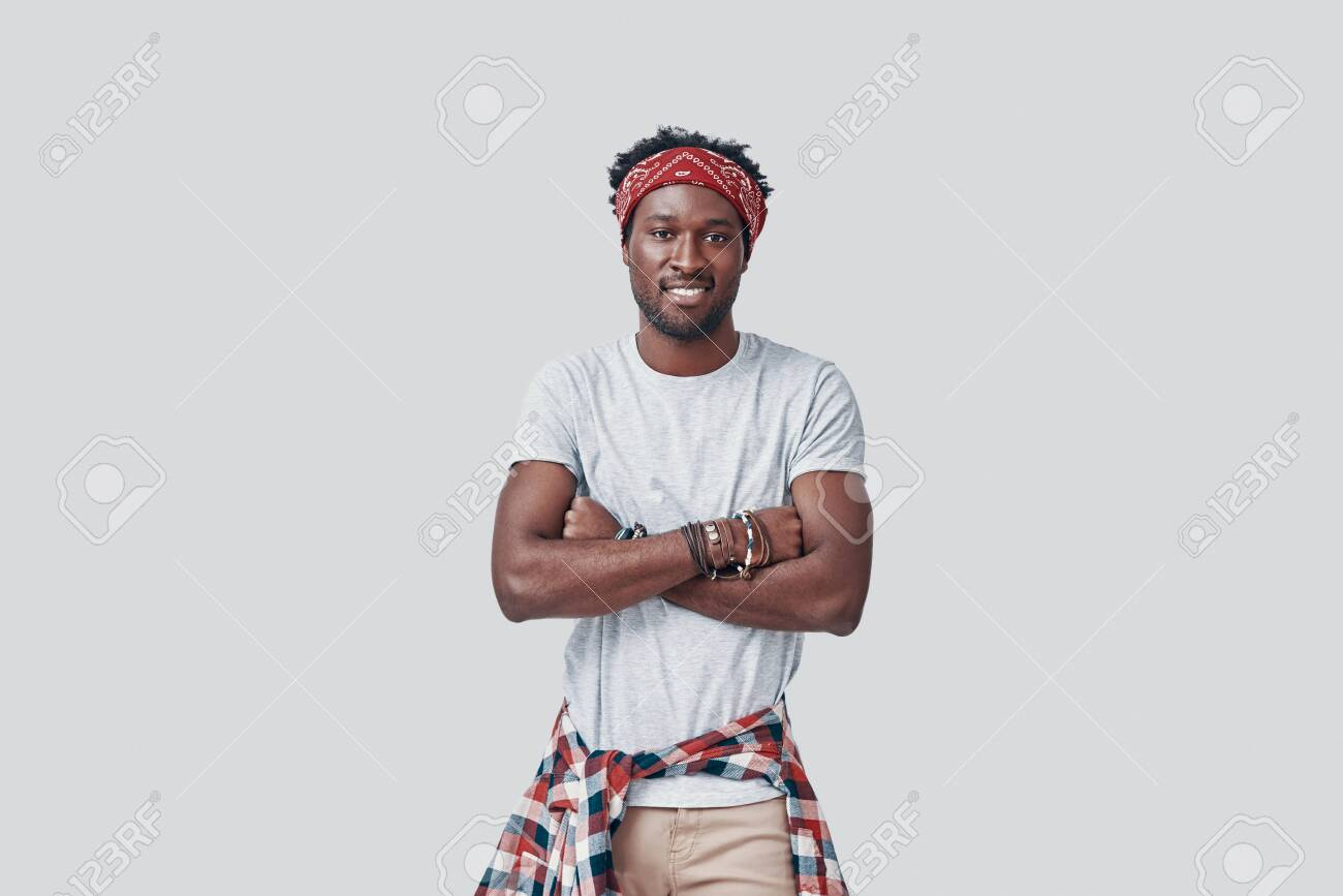 Handsome young African man looking at camera and smiling while standing against grey background - 135471616