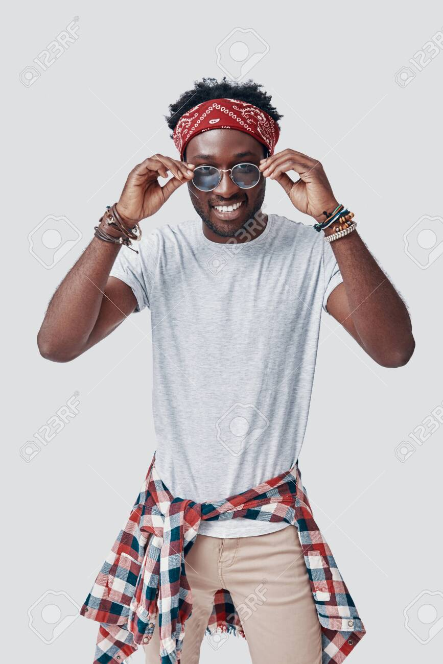 Handsome young African man adjusting his eyewear and looking at camera while standing against grey background - 135471618
