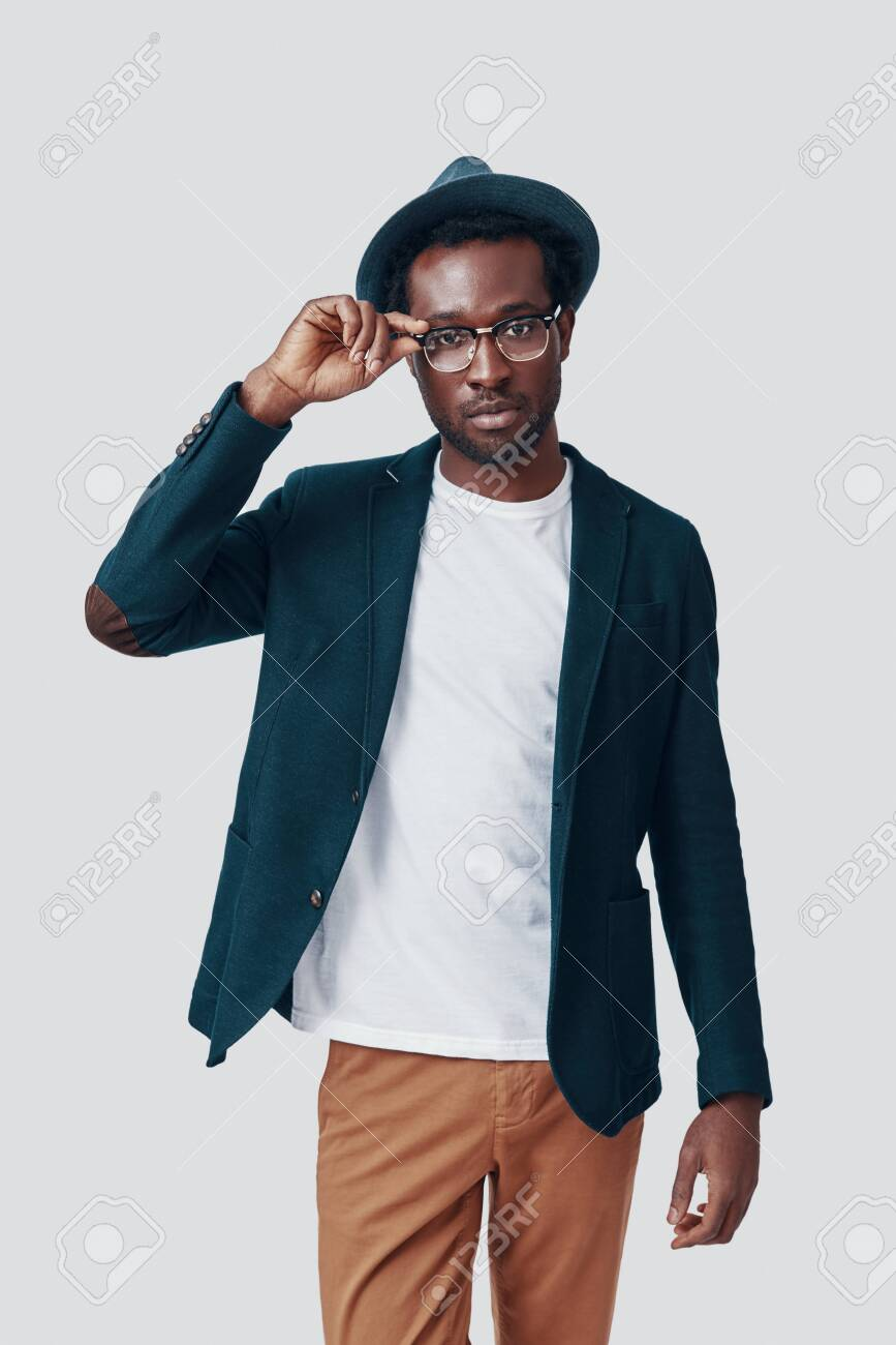 Handsome young African man adjusting eyewear and looking at camera while standing against grey background - 135471625