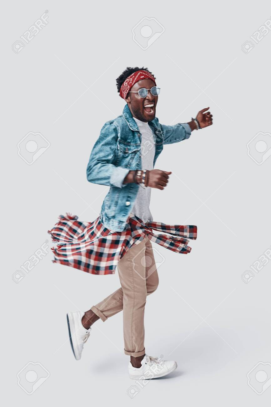 Full length of handsome young African man smiling while standing against grey background - 135471629