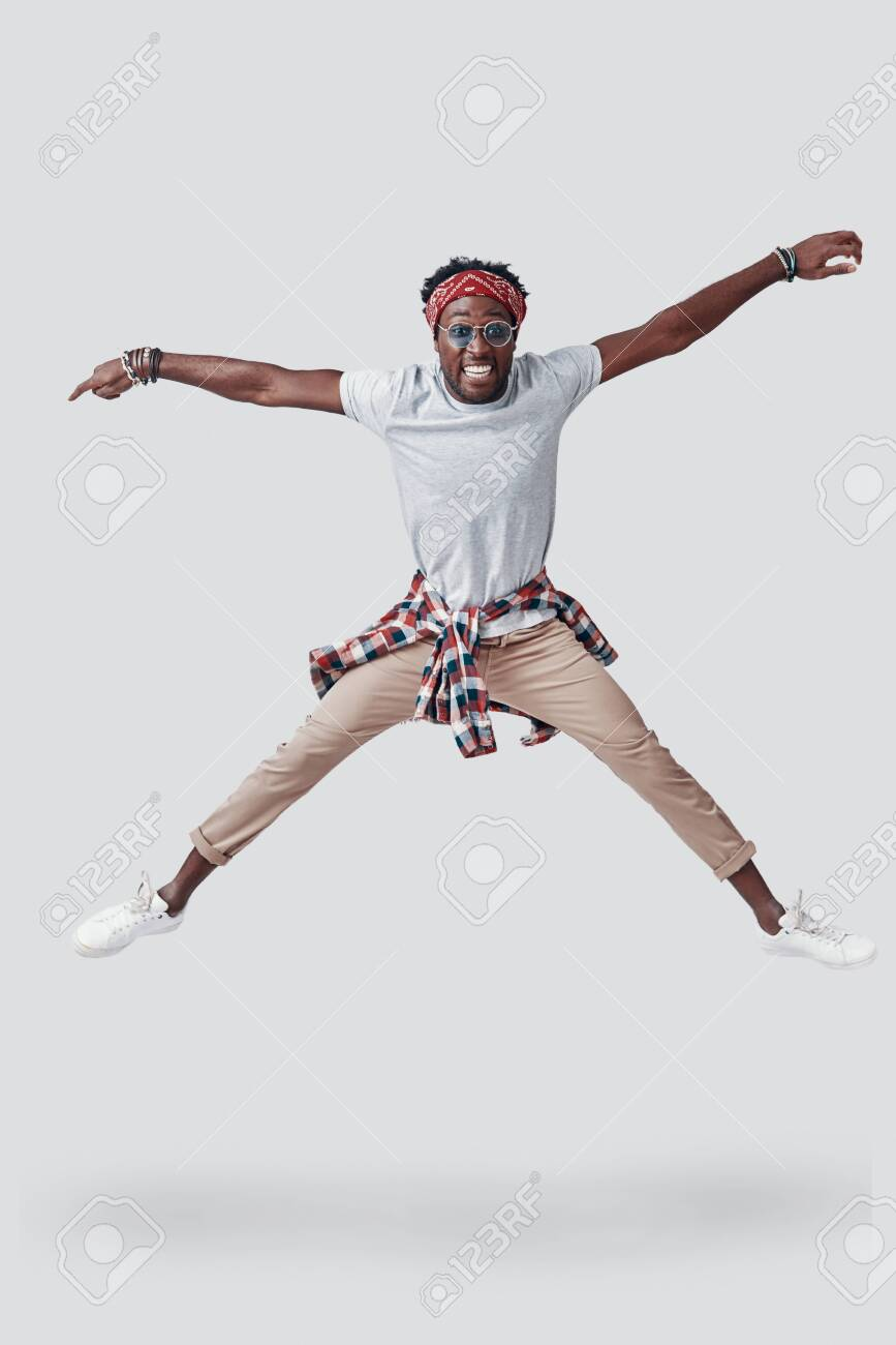 Full length of playful young African man smiling and looking at camera while hovering against grey background - 135471632