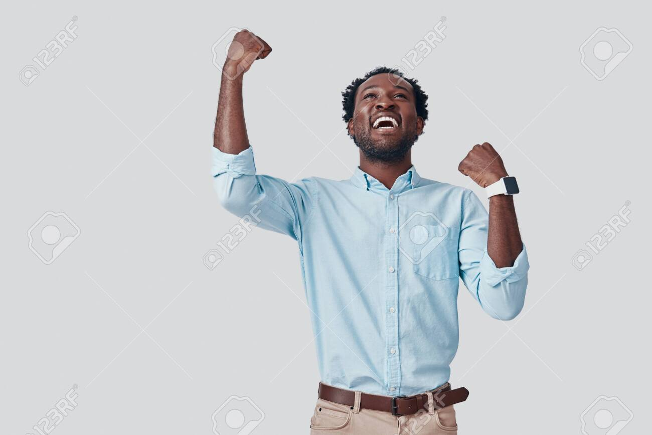 Handsome young African man gesturing and smiling while standing against grey background - 135471634