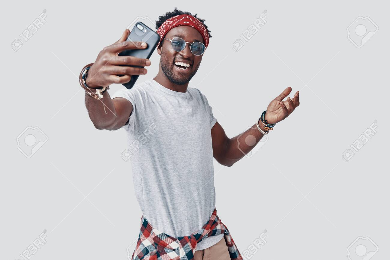 Handsome young African man taking selfie and smiling while standing against grey background - 135471642