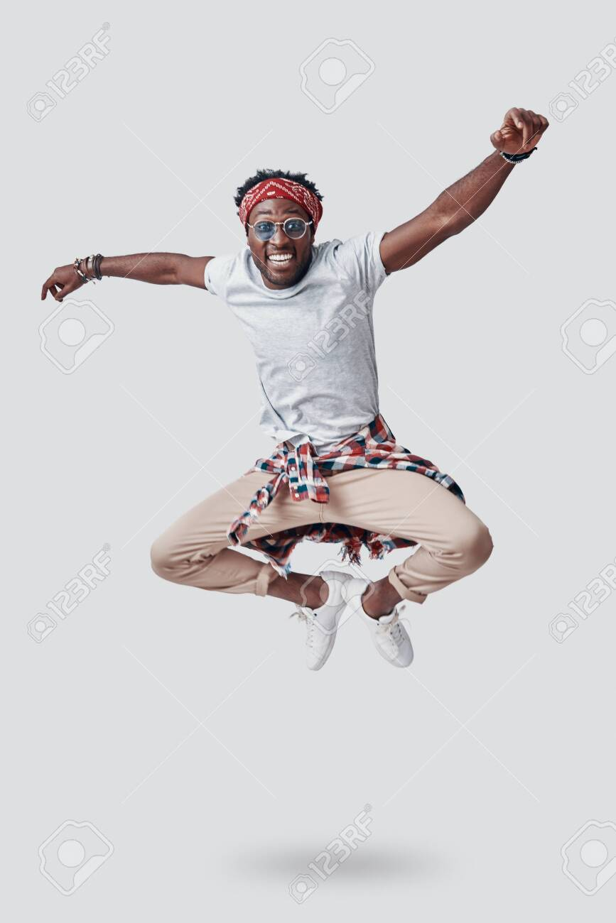 Full length of playful young African looking at camera and smiling while hovering against grey background - 135471644