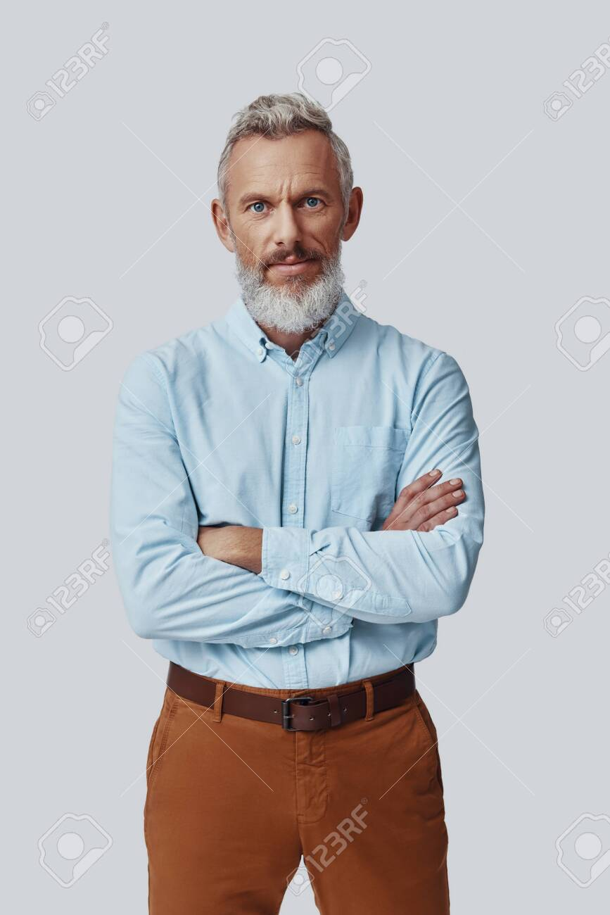 Confident mature man looking at camera and keeping arms crossed while standing against grey background - 138444907