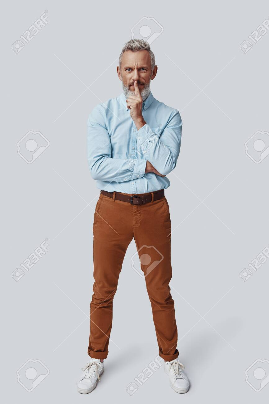 Full length of mature man looking at camera and keeping finger on lips while standing against grey background - 138444909