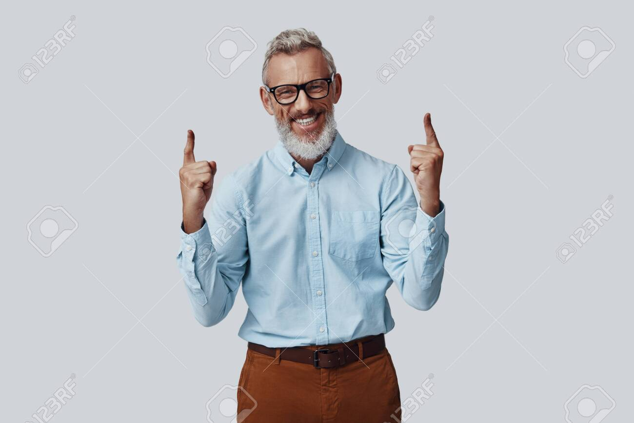 Cheerful mature man smiling and pointing copy space while standing against grey background - 138444943