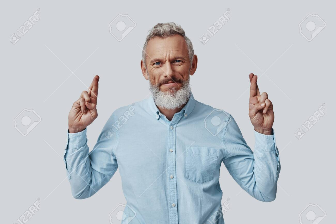 Mature man looking at camera and keeping fingers crossed while standing against grey background - 137917217