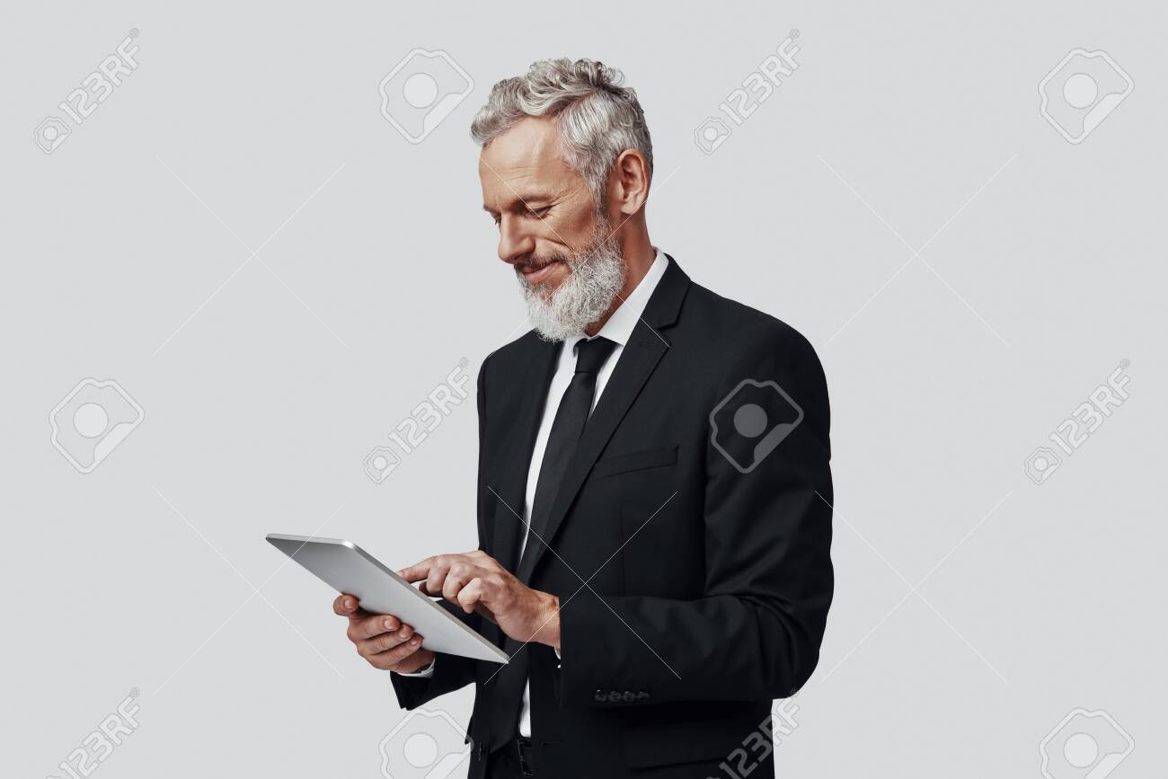 Thoughtful mature man in full suit working using digital tablet and smiling while standing against grey background - 137917279