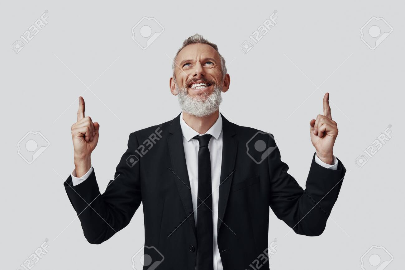 Happy mature man in full suit pointing copy space and smiling while standing against grey background - 137917172