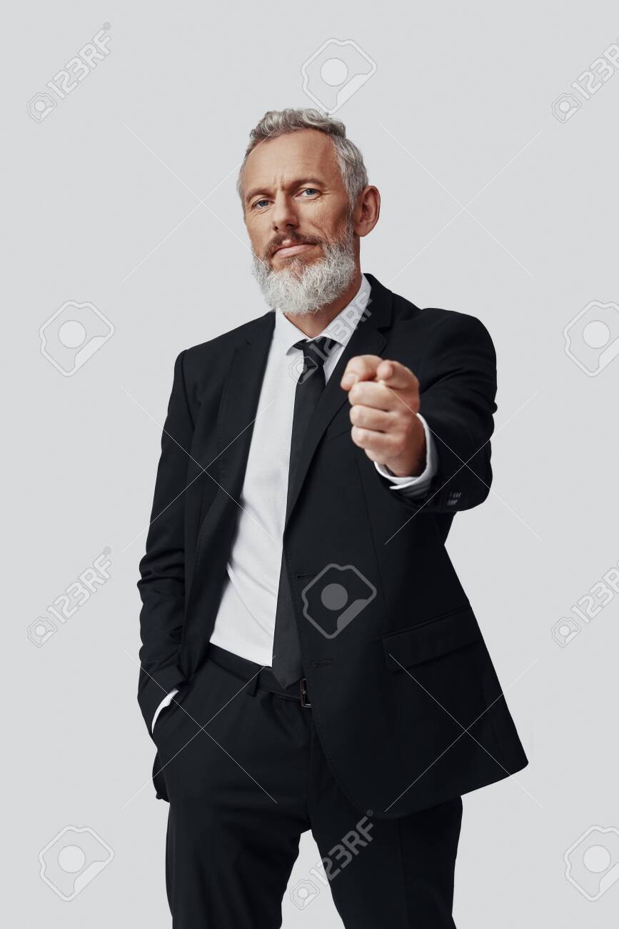 Confident mature man in full suit pointing you and looking at camera while standing against grey background - 137917327