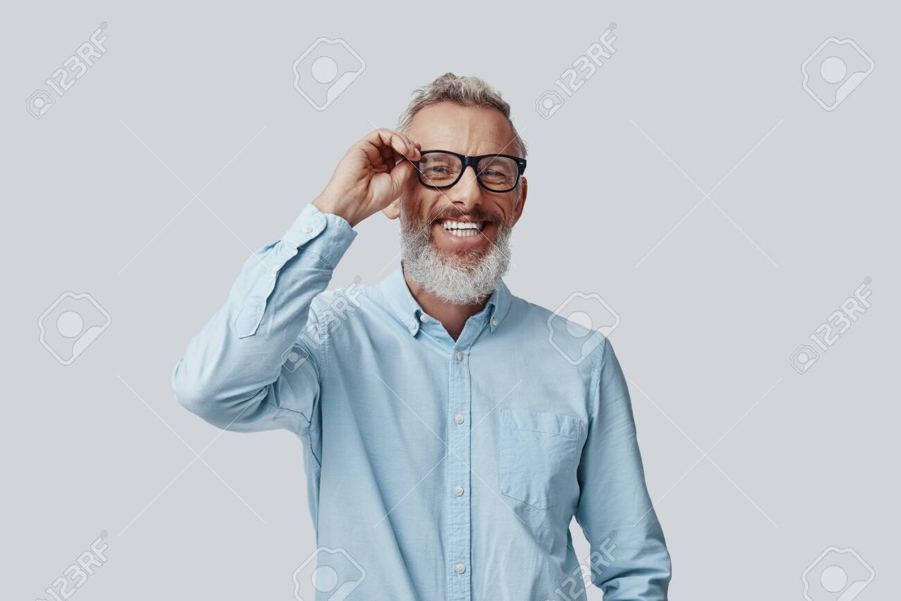 Happy mature man looking at camera and adjusting eyewear while standing against grey background - 138444956