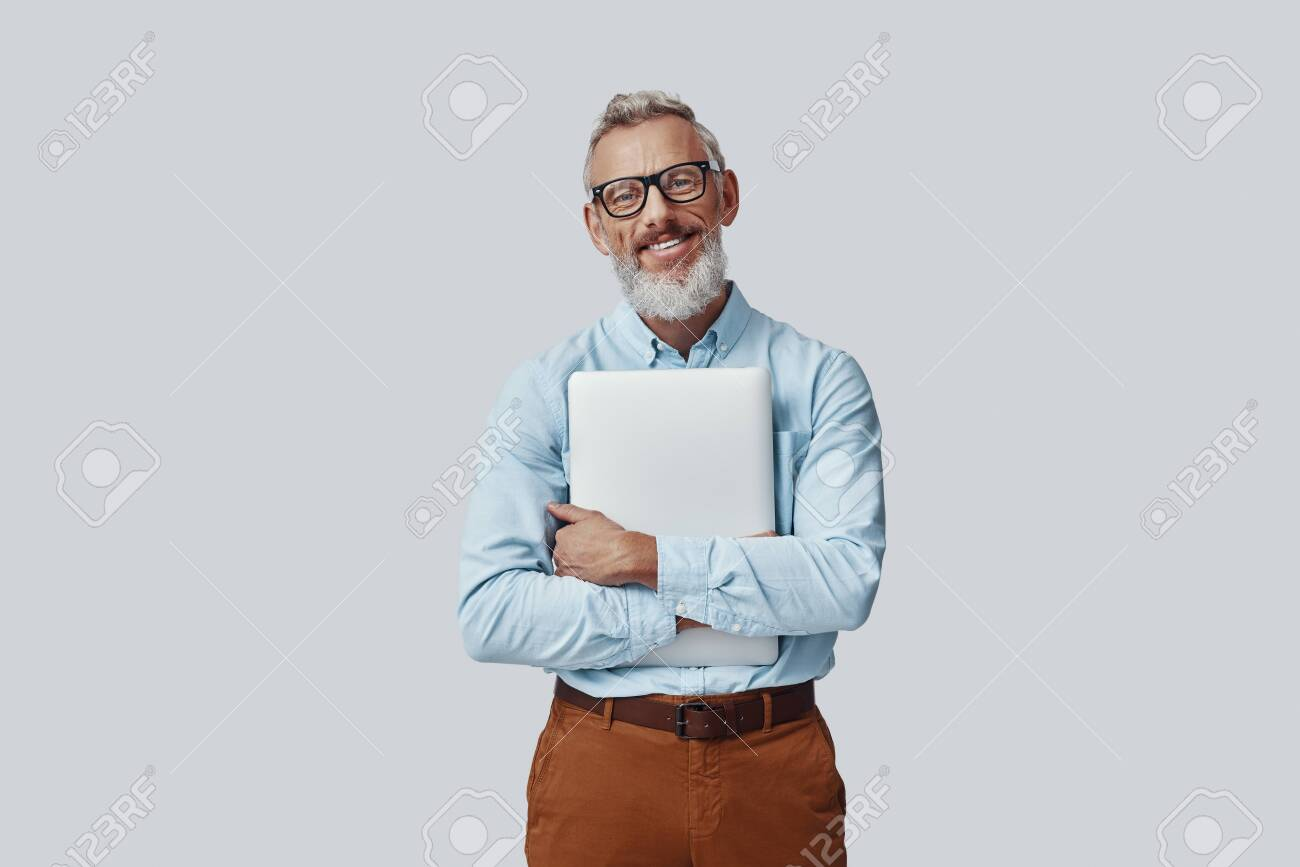 Happy mature man smiling and carrying laptop while standing against grey background - 137917550