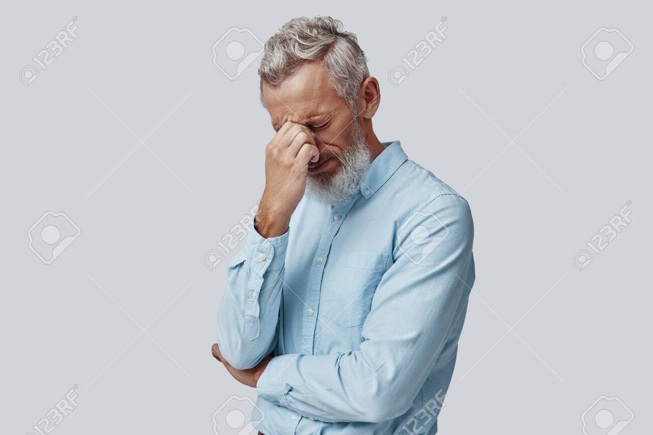 Tired mature man suffering from headache while standing against grey background - 137362930