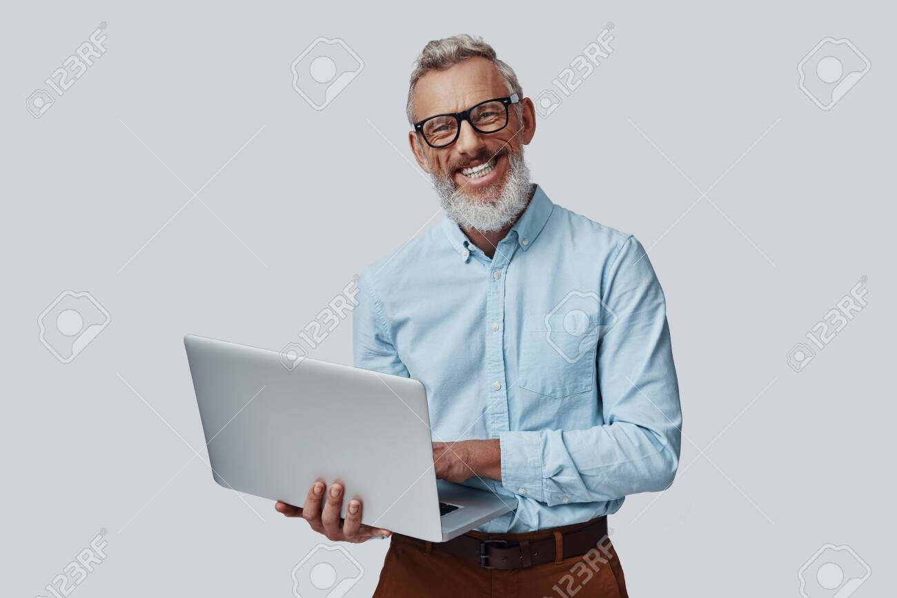 Happy mature man smiling and working using laptop while standing against grey background - 137922708