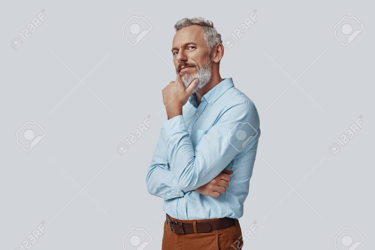 Thoughtful mature man looking at camera and keeping hand on chin while standing against grey background - 138445034