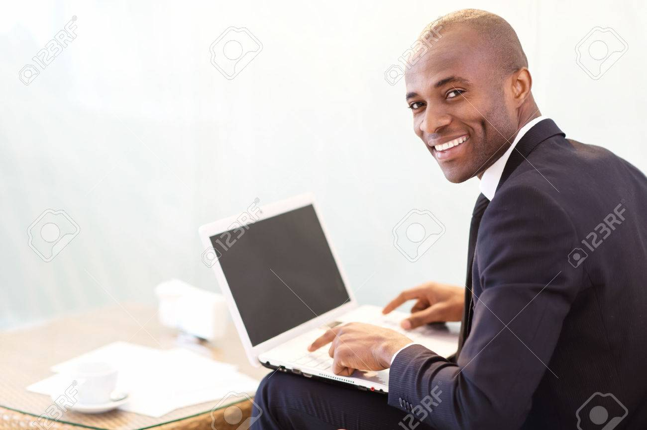Businessman with laptop. Cheerful young African businessman typing something on laptop and looking over shoulder Stock Photo - 24487818