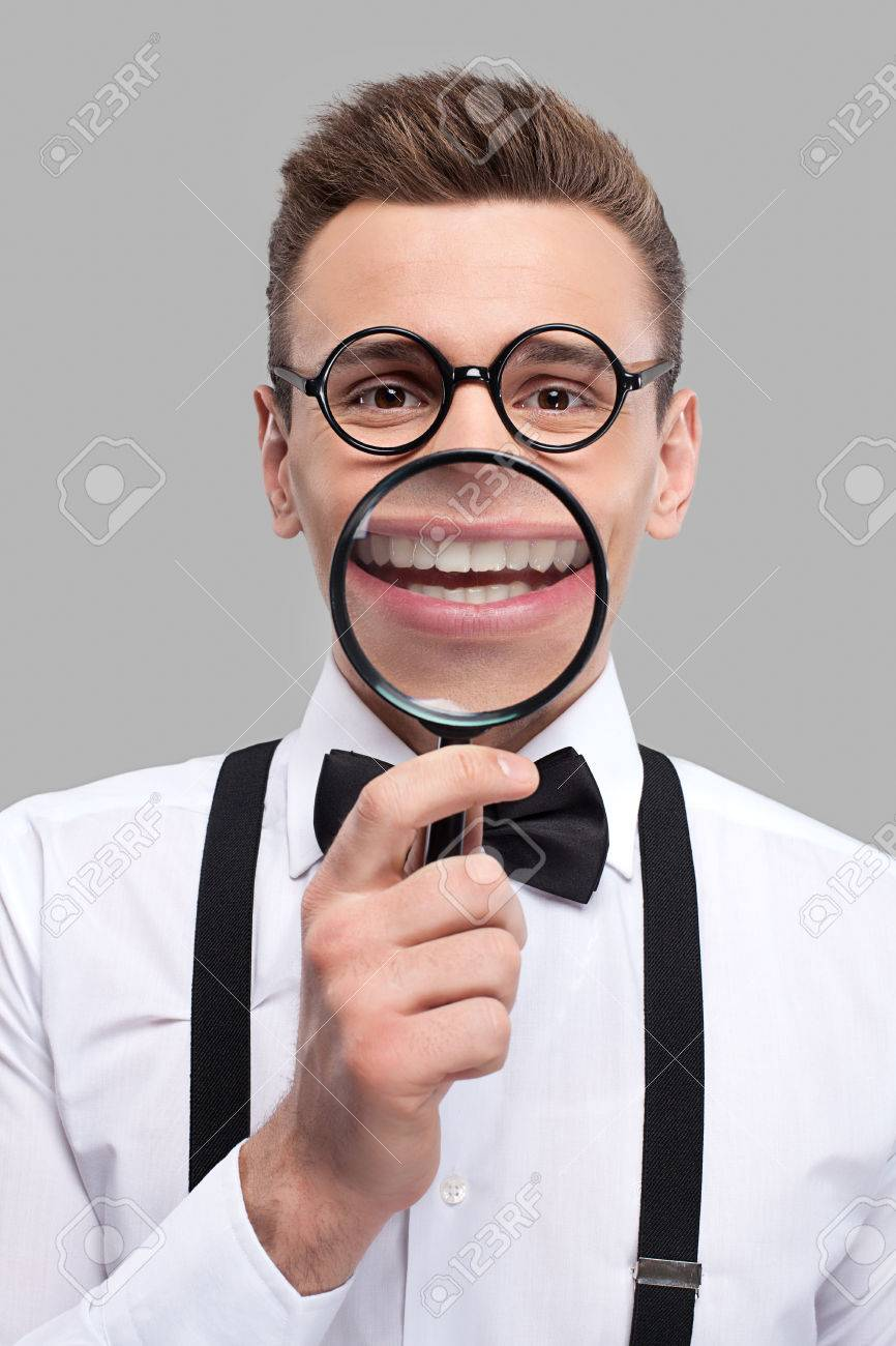 abd27d03c914 Magnifying smile. Portrait of cheerful young man in bow tie and suspenders  holding magnifying glass