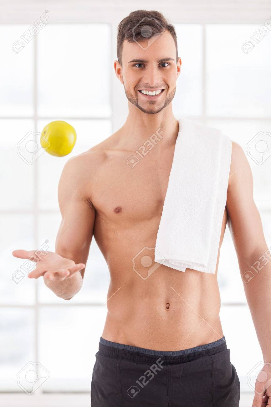 Handsome young muscular man with towel on shoulder throwing up an apple 0351ad75f