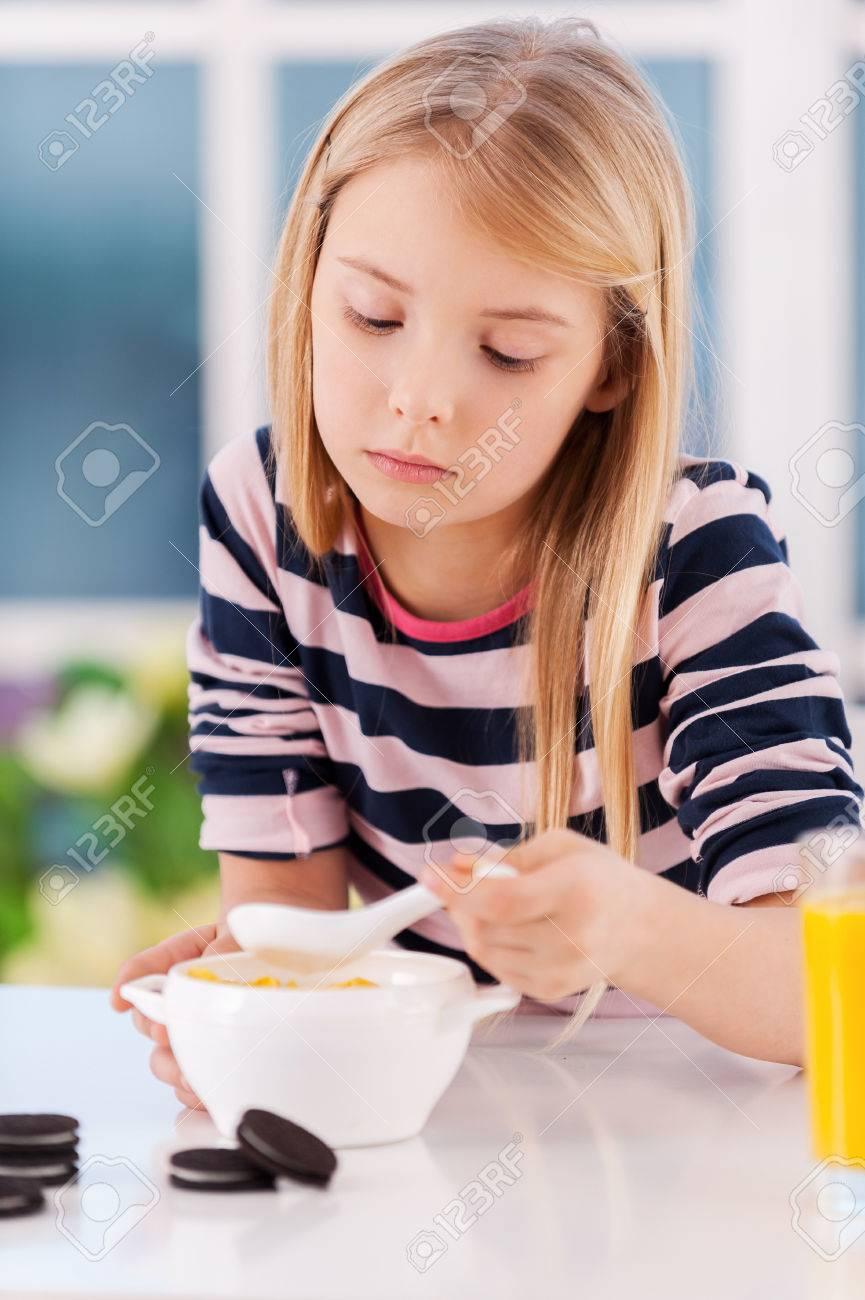 I am not hungry sad little girl eating something from the plate while sitting at