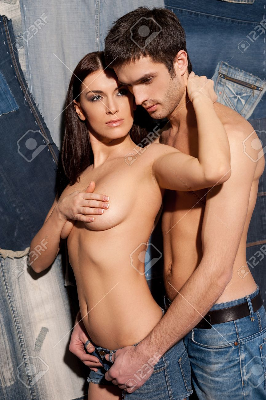 Hot denim couple. Beautiful young shirtless couple hugging while standing against jeans background Stock Photo - 26313135