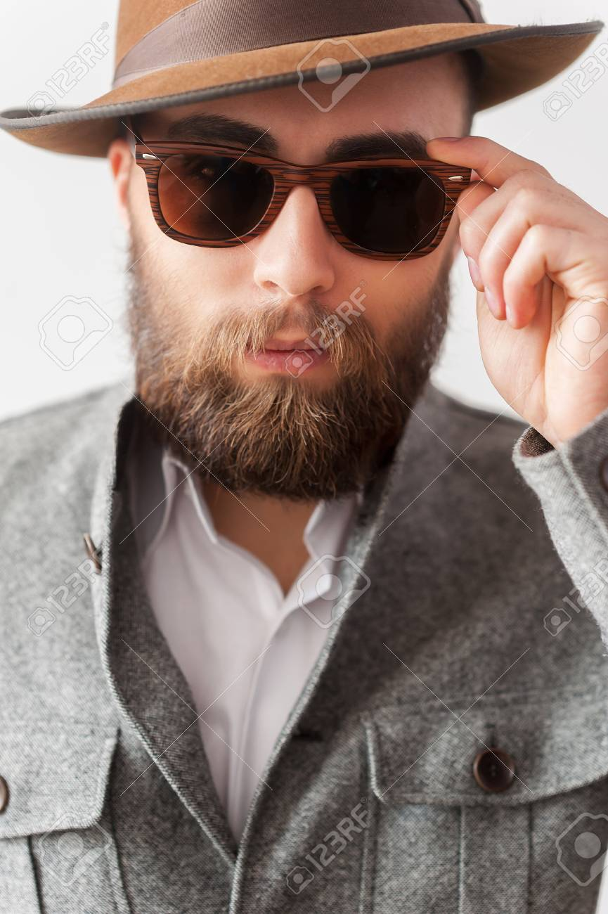 Stock Photo - Trendy look. Close up portrait of handsome young man in  casual wear adjusting his sunglasses 84d66e8940b3