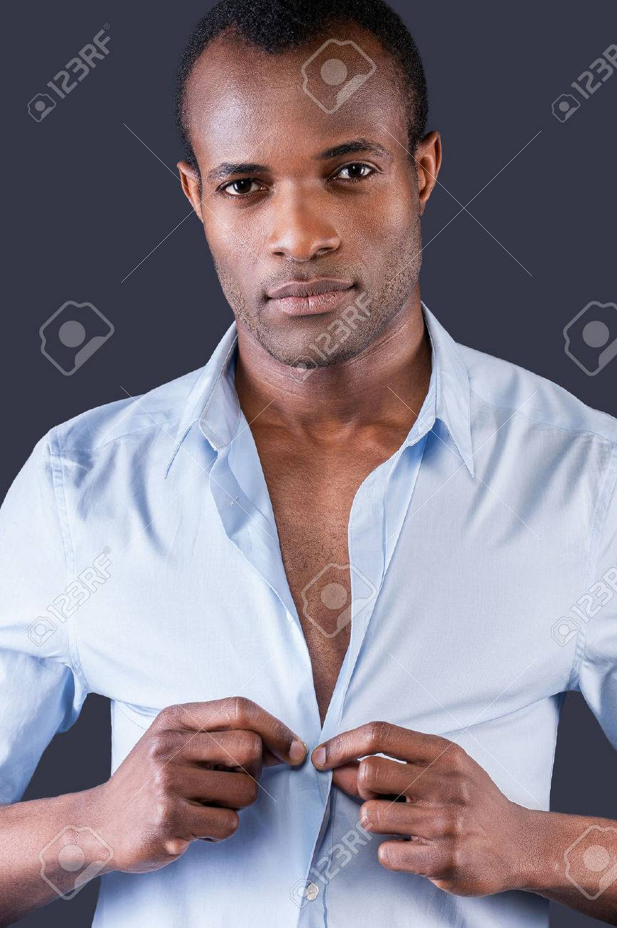 162e335dd Stock Photo - Wearing his favorite shirt. Handsome young black man dressing  up his shirt and smiling at camera while standing against grey background