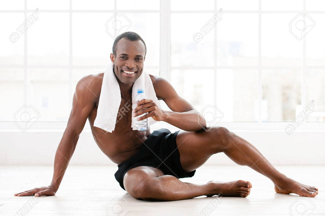 7649697e9 Keeping his body in shape. Cheerful young African man sitting on the floor  and holding