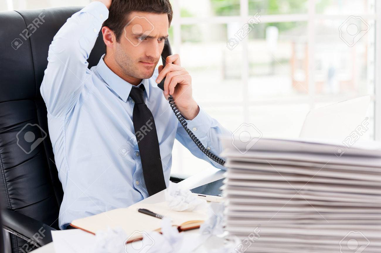 Frustrated office worker on the phone holding stock photo image - Busy Office Life Frustrated Young Man In Formalwear Talking On The Telephone And Holding Hand