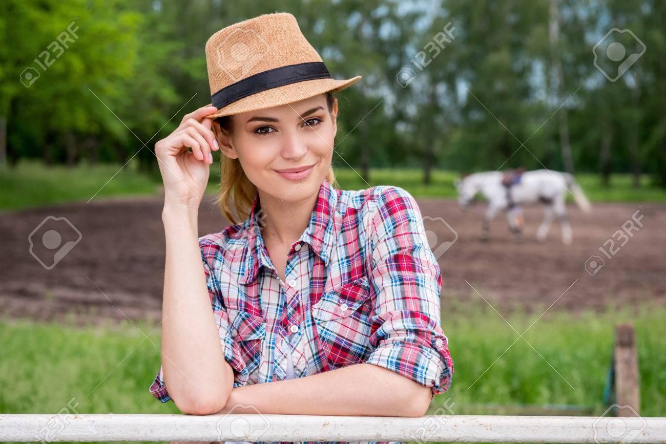 Mujer joven hermosa que ajusta su sombrero de vaquero y sonriente mientras  está 687701f4d67